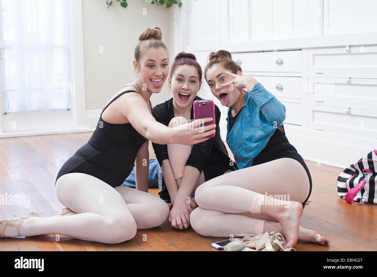 Three teenage girls taking smartphone selfie in ballet school - Stock Image