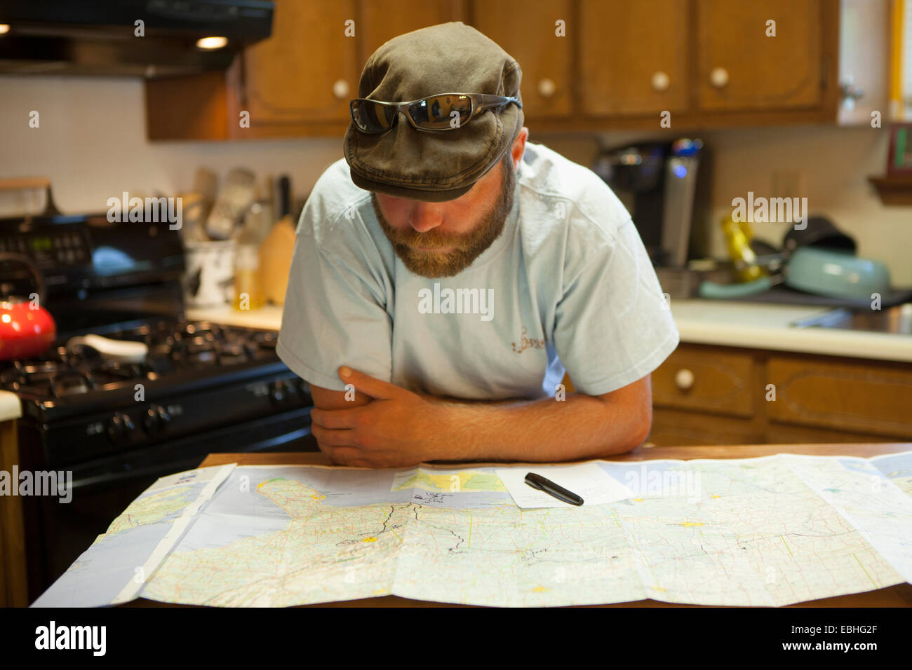 Man studying map of USA at kitchen table - Stock Image