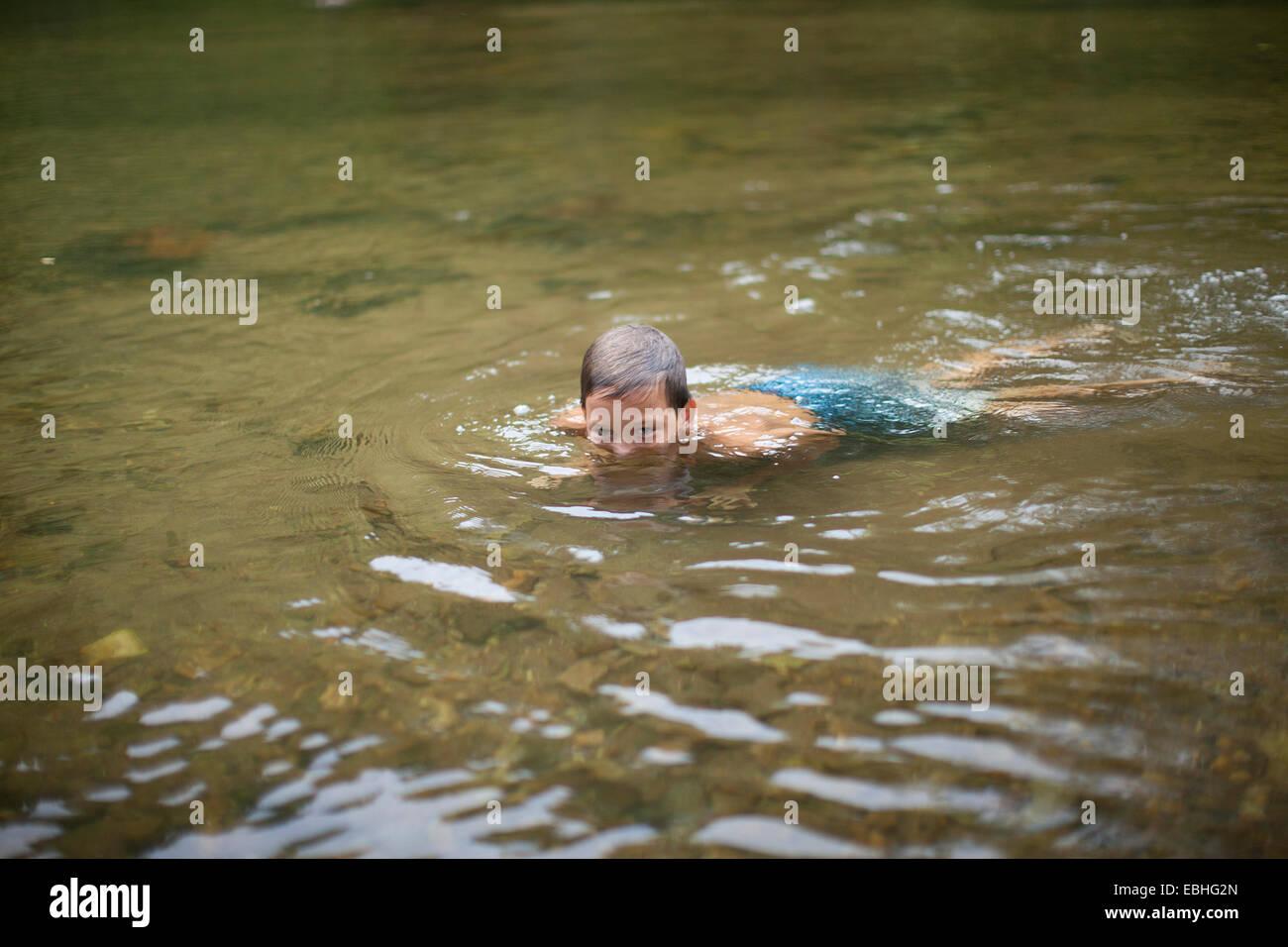 Teenage boy submerged in river, Canton, North Carolina, USA - Stock Image