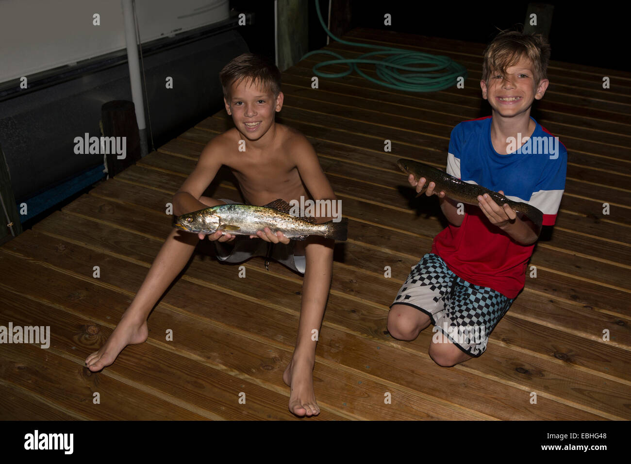 Two brothers on pier at night holding spanish mackerel fish, Shalimar, Florida, USA - Stock Image
