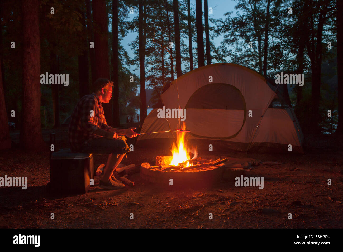 Man cooking on campfire in forest at night, Arkansas, USA - Stock Image
