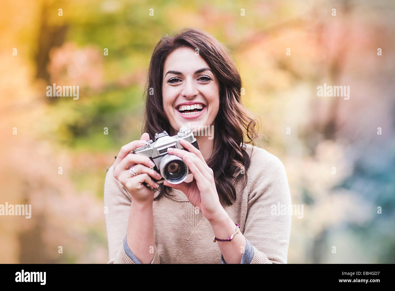 Portrait of smiling young woman using SLR camera in autumn forest - Stock Image