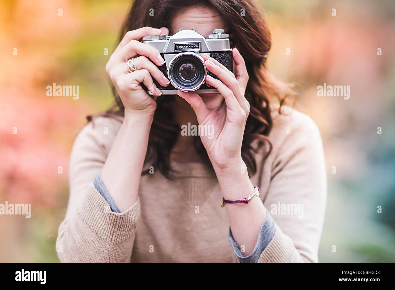 Young woman photographing with SLR camera in autumn forest - Stock Image