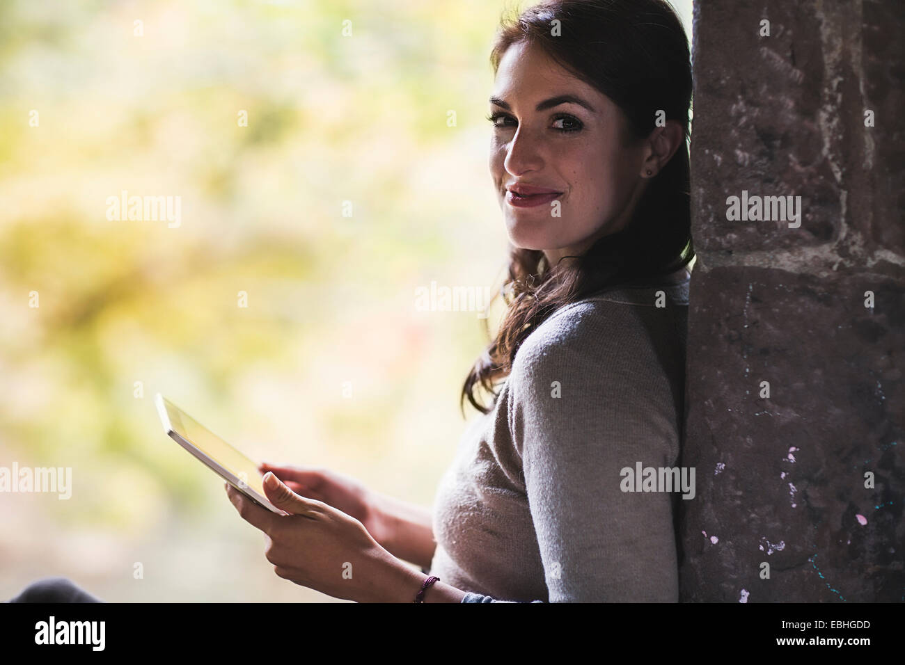 Portrait of young woman leaning against wall using digital tablet - Stock Image