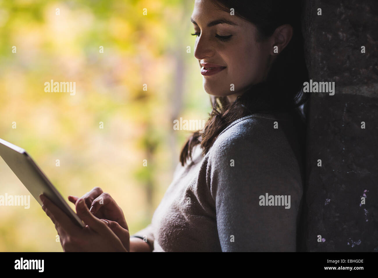 Young woman leaning against wall using touchscreen on digital tablet - Stock Image