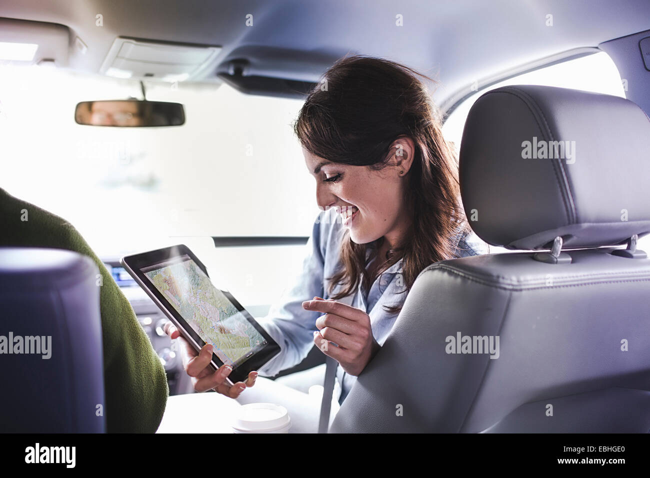 Over shoulder view of young woman in car front seat using digital tablet map - Stock Image