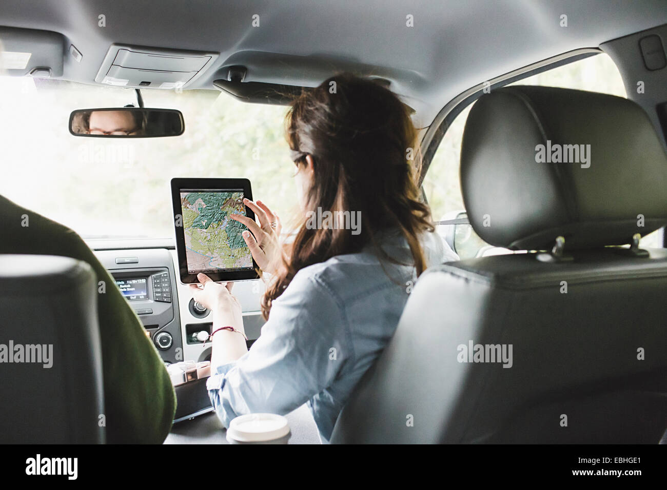 Over shoulder view of young woman in car front seat using digital tablet touchscreen map - Stock Image