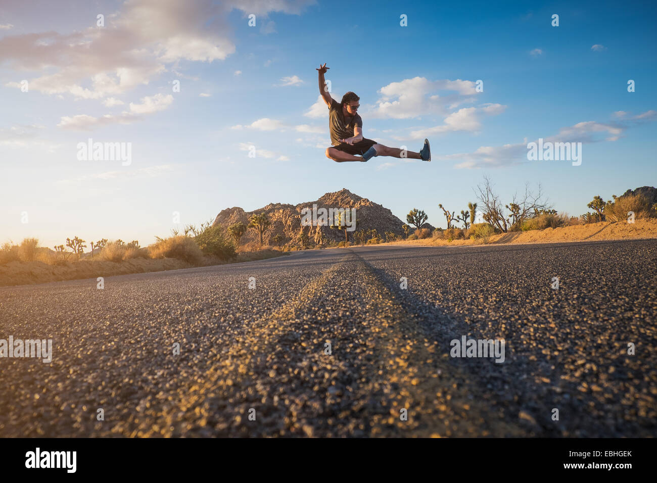 Man doing flying kick, Joshua Tree National Park, California, US - Stock Image