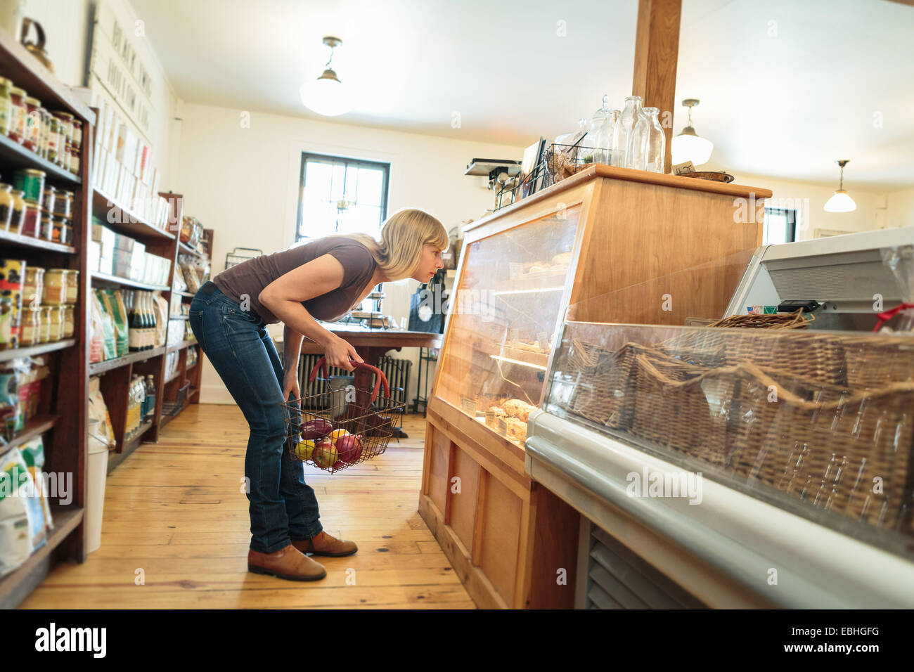 Female customer leaning to look at display cabinet in country store - Stock Image