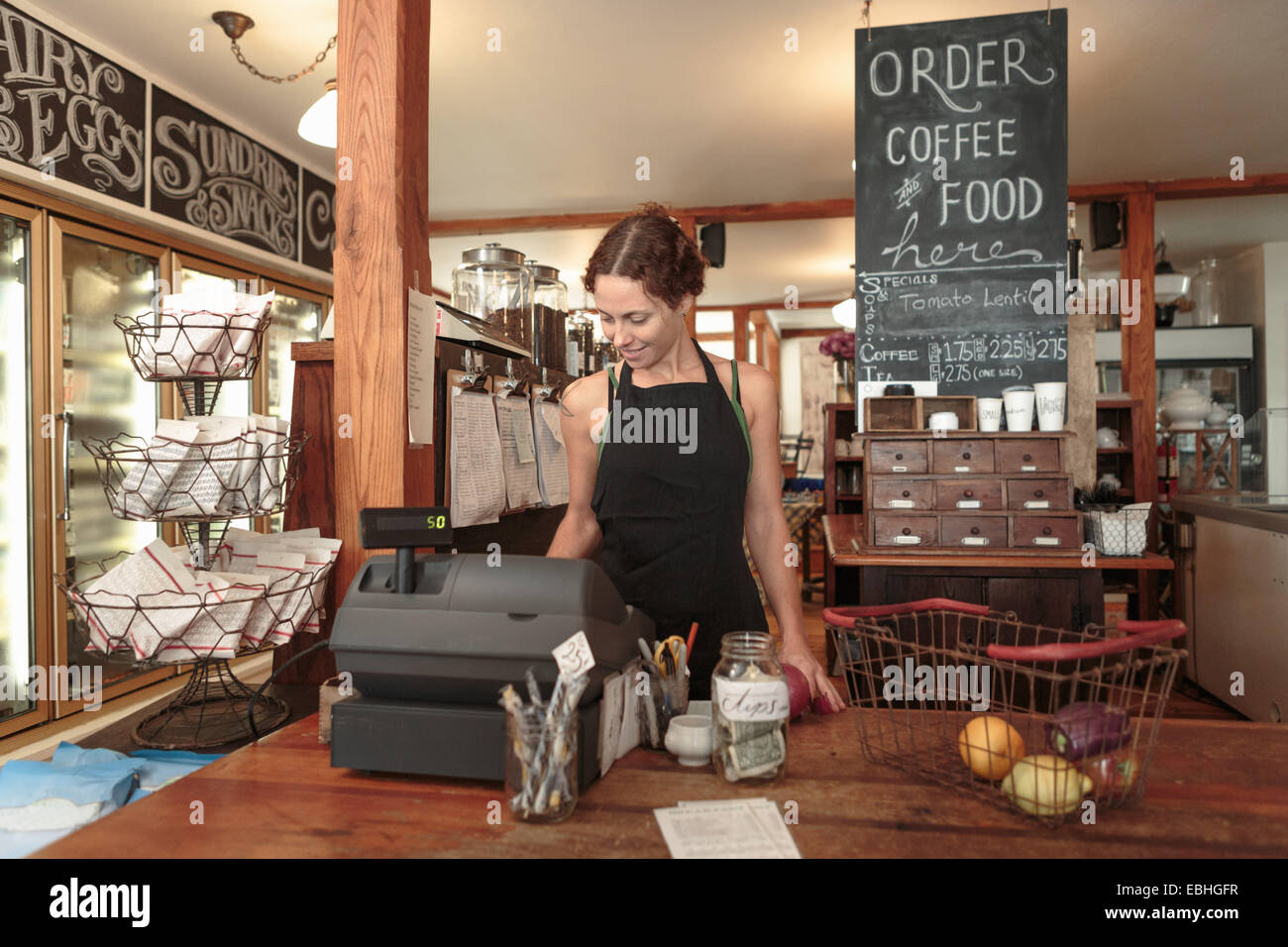 Female sales assistant using check out till in country store cafe - Stock Image
