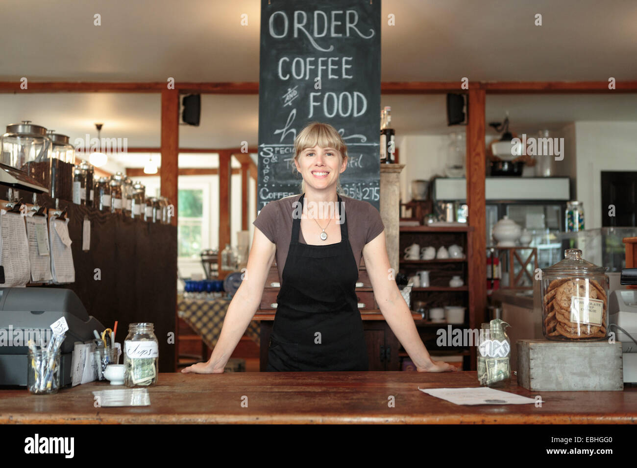 Portrait of female shop assistant in country store cafe - Stock Image