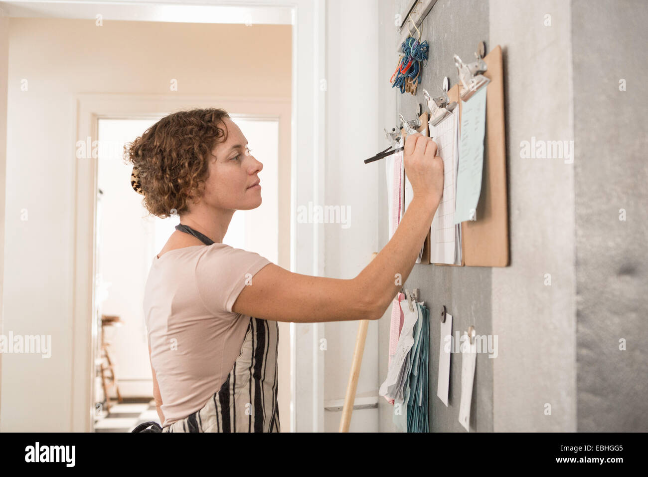Female shop assistant writing on wall clipboards in kitchen at country store - Stock Image