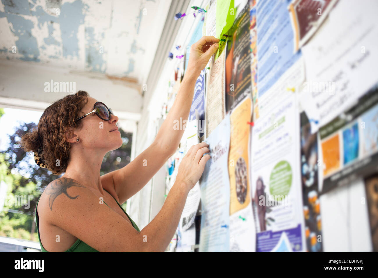 Mid adult woman pinning up notice on community notice board - Stock Image