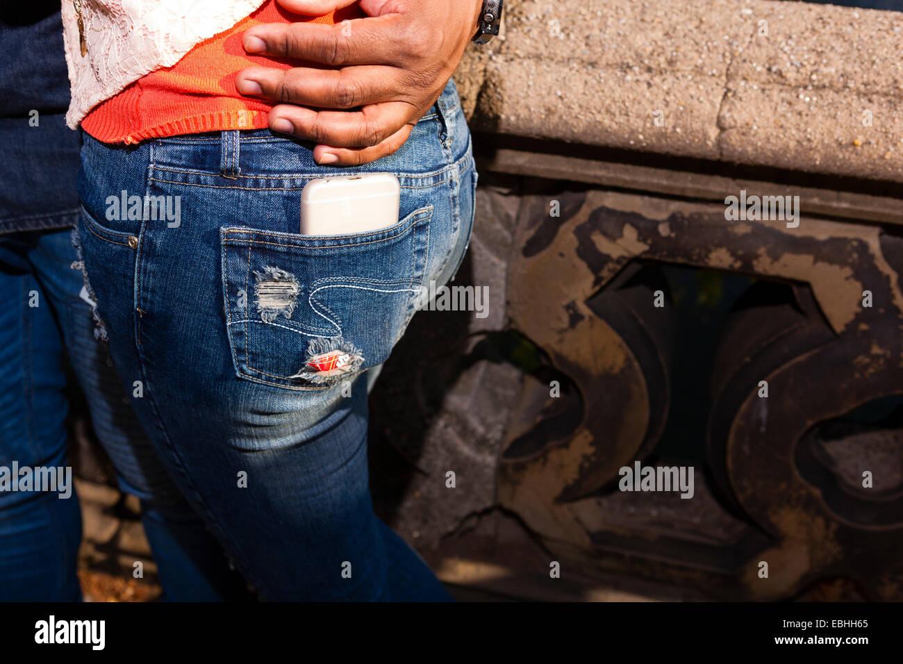 Smartphone in back pocket of jeans - Stock Image