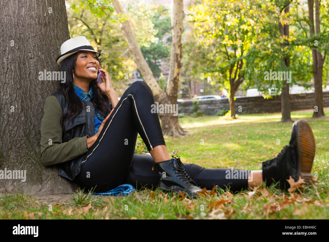 Young woman sitting against tree using smartphone - Stock Image