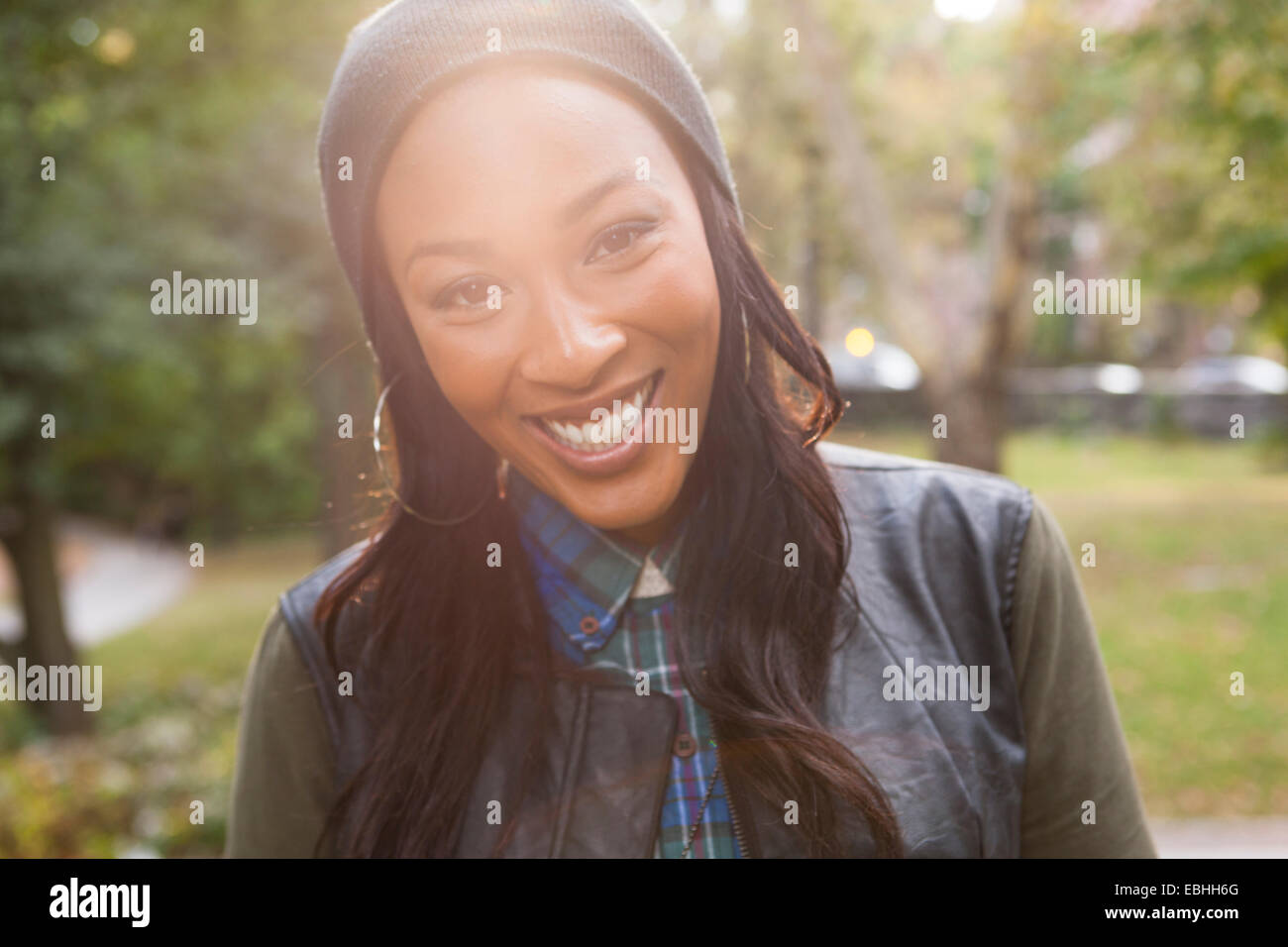 Young woman with wide smile in park - Stock Image