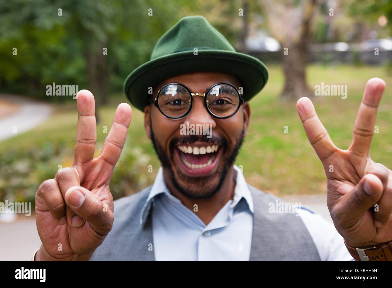 Man making peace sign smiling widely in park - Stock Image