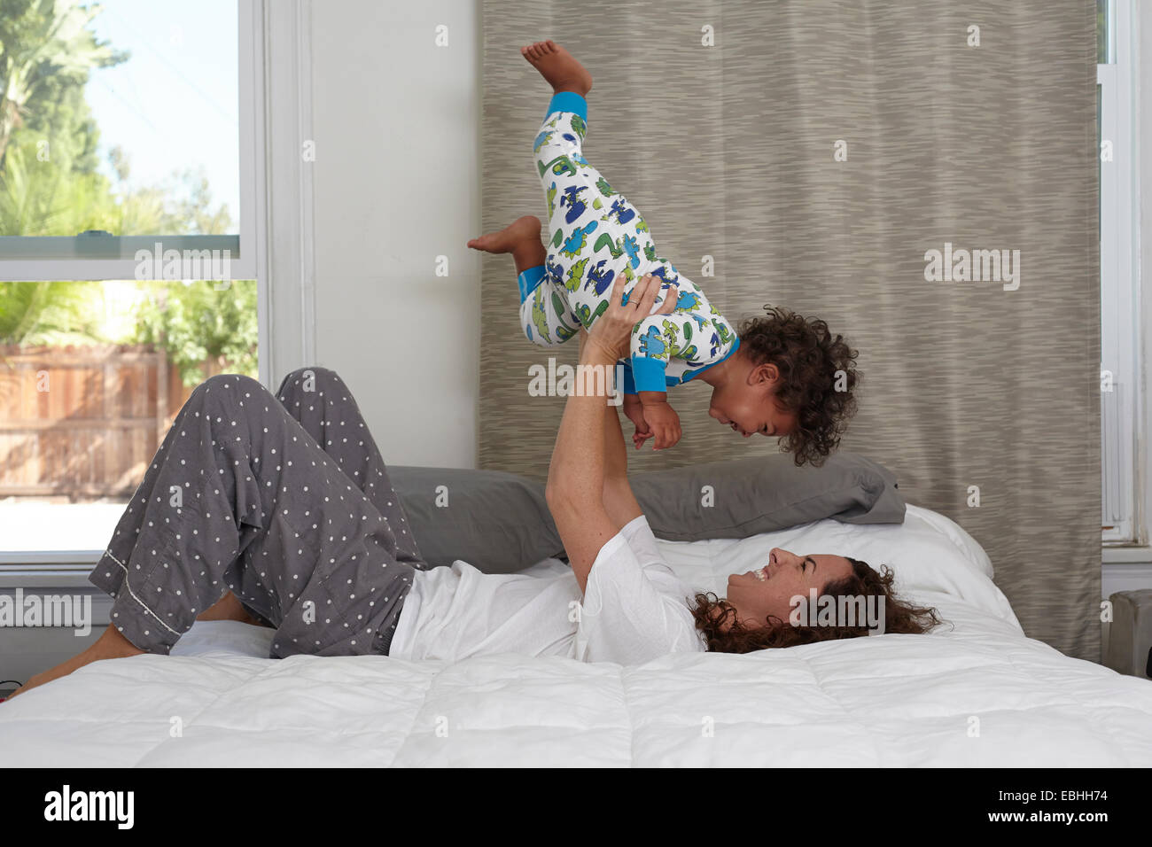 Young woman lying on bed lifting up toddler son - Stock Image