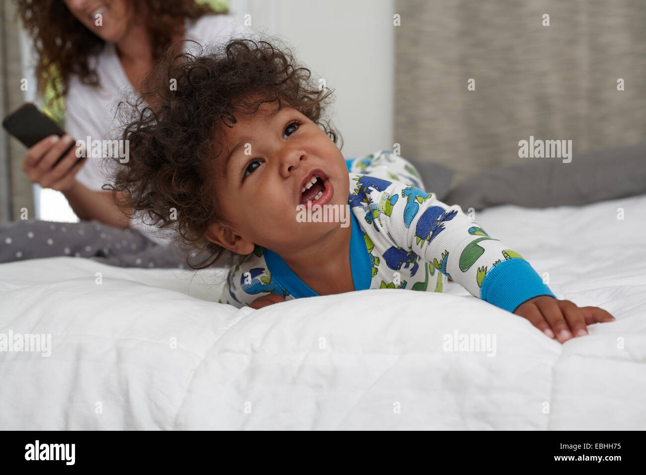 Male toddler crawling on bed whilst mother using smartphone - Stock Image