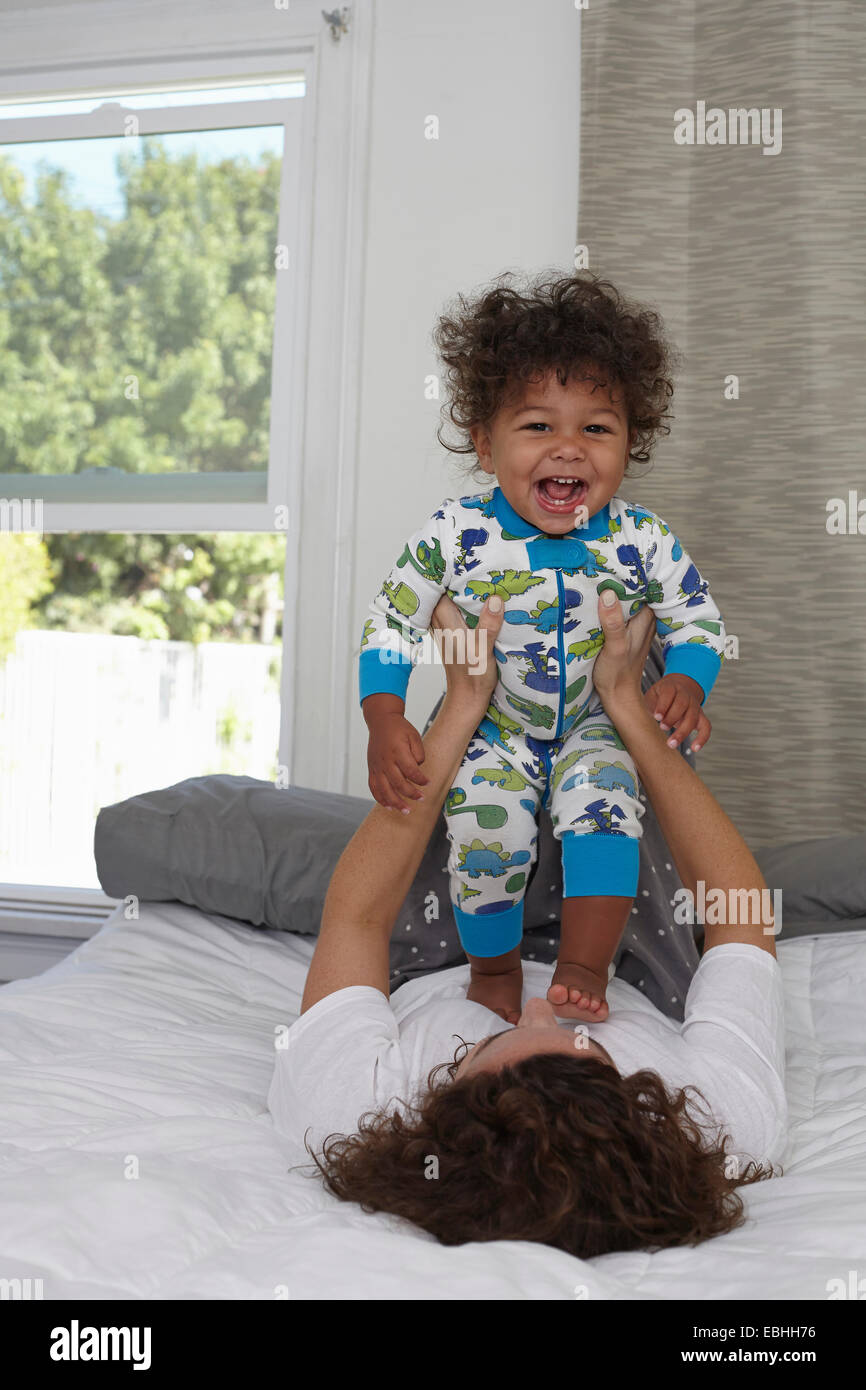 Young woman lying on bed holding up toddler son - Stock Image