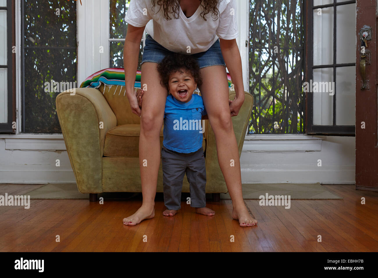 Male toddler taking first steps with mother in sitting room - Stock Image