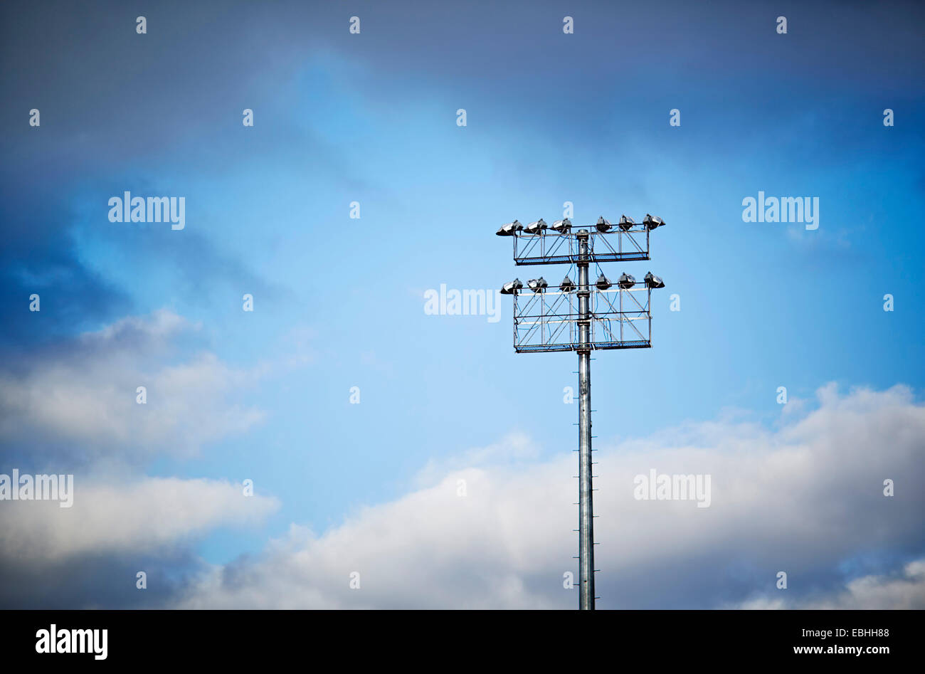 Low angle view of stadium floodlight and blue sky - Stock Image