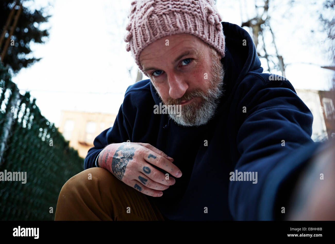 Mature man crouching with arm out to take self portrait - Stock Image