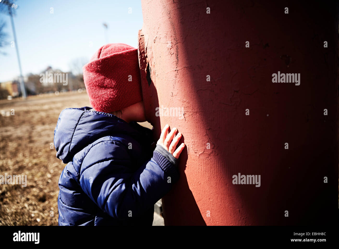 Male toddler playing hide and seek in park - Stock Image