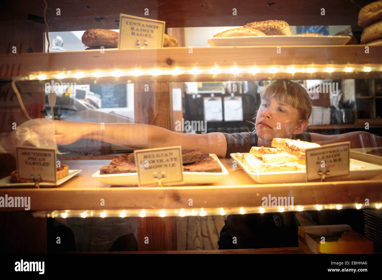 Female shop assistant picking up cake from display cabinet in country store - Stock Image