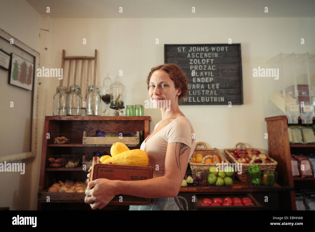 Portrait of female shop assistant carrying fruit and veg crate in country store - Stock Image