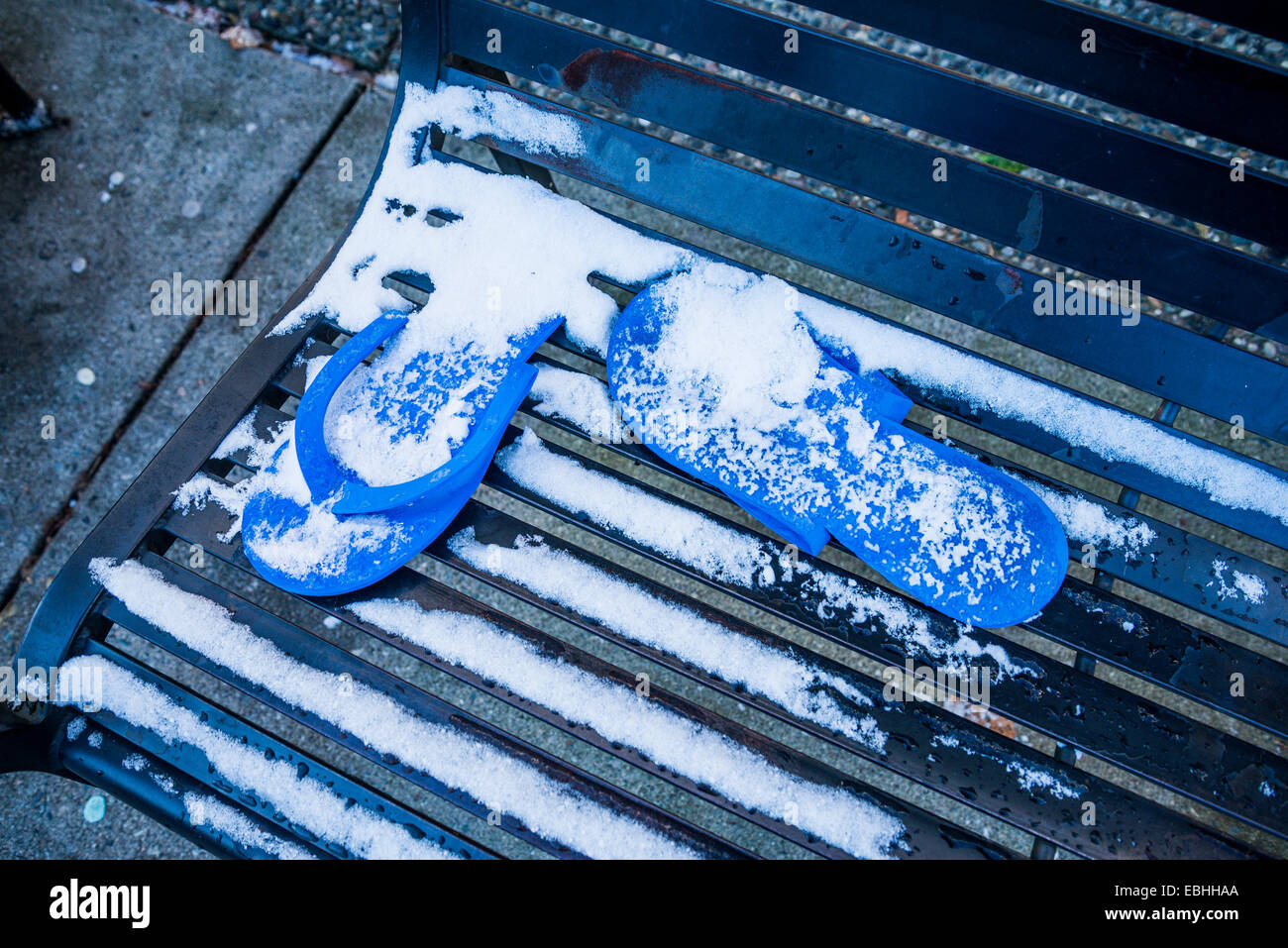 Flip flop sandals left behind on bench with snow. - Stock Image