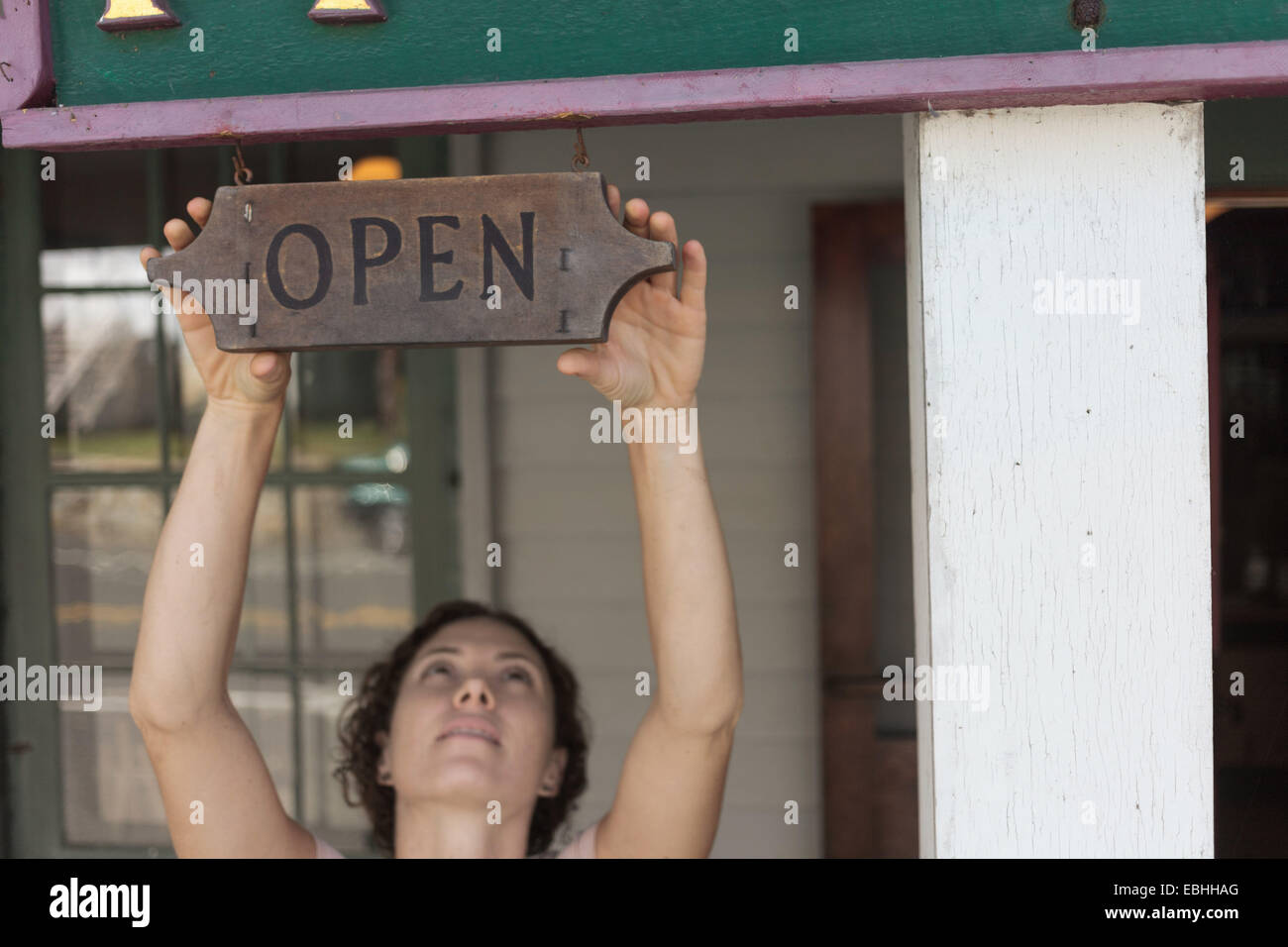Female shop assistant reaching for open sign at country store - Stock Image