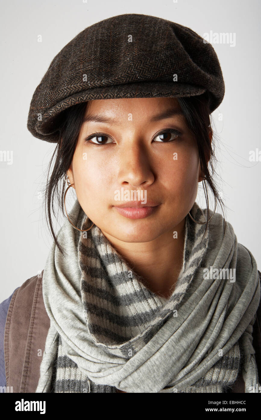 Studio portrait of mid adult woman wearing flat cap and scarf - Stock Image f723c85fe7f