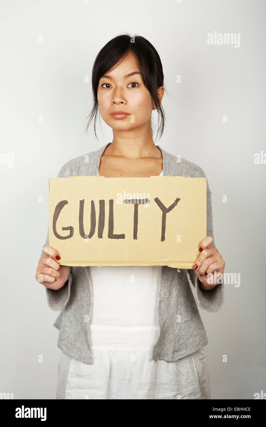 Studio portrait of mid adult woman holding up guilty sign - Stock Image
