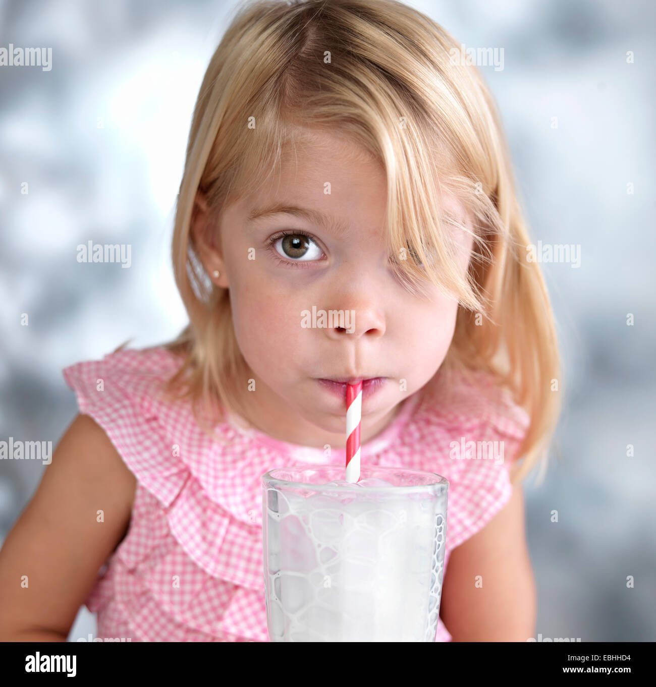 Portrait of female toddler blowing bubbles in milk through drinking straw - Stock Image