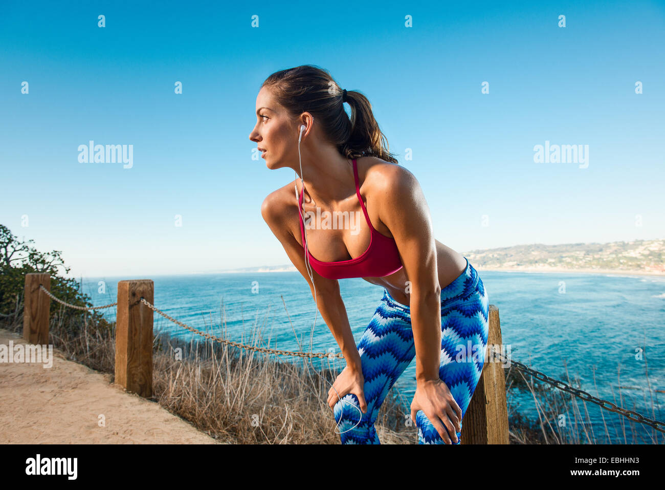 Young woman doing stretches by sea - Stock Image