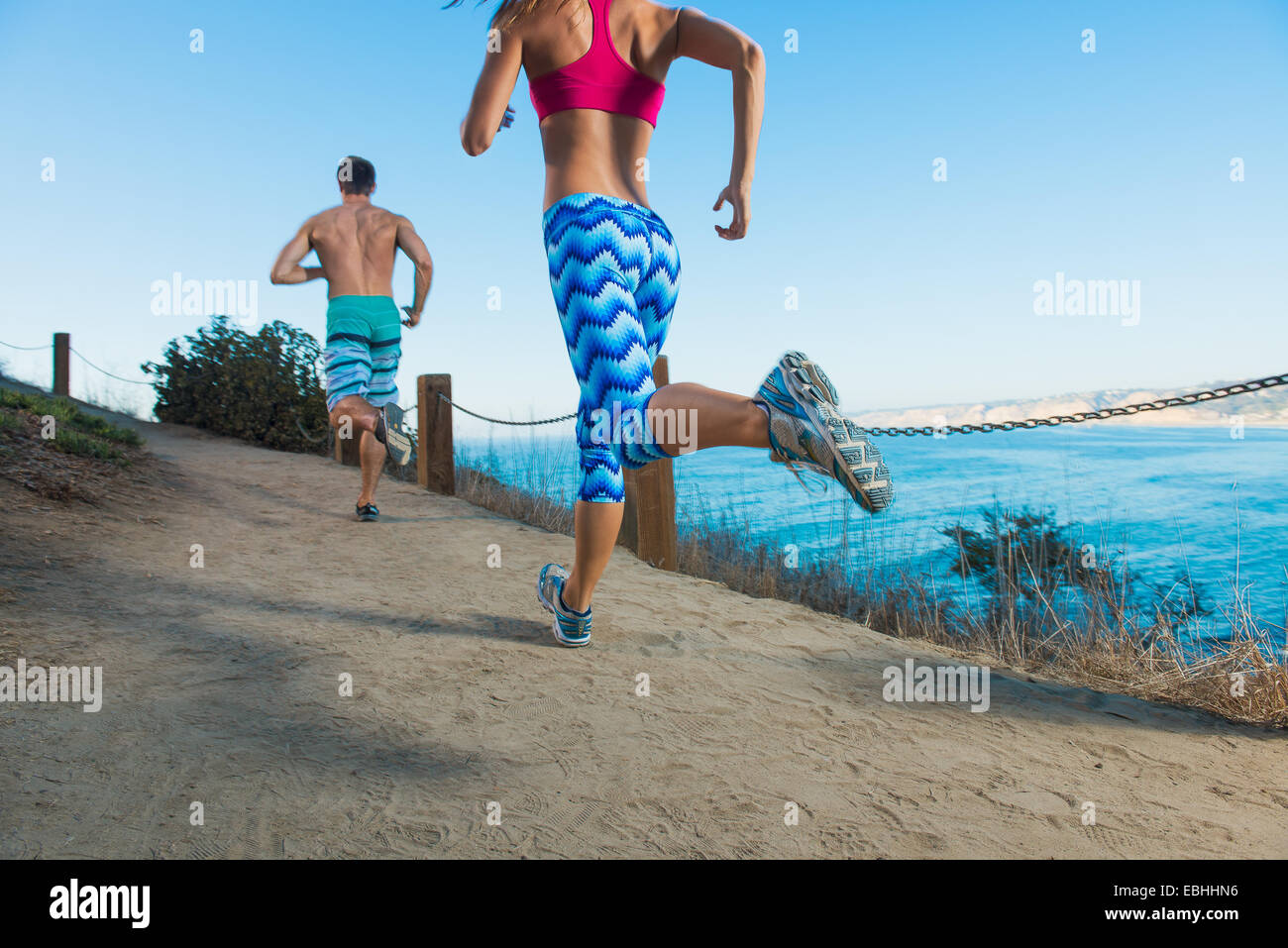 Mid adult man and young woman running on path by sea, rear view Stock Photo