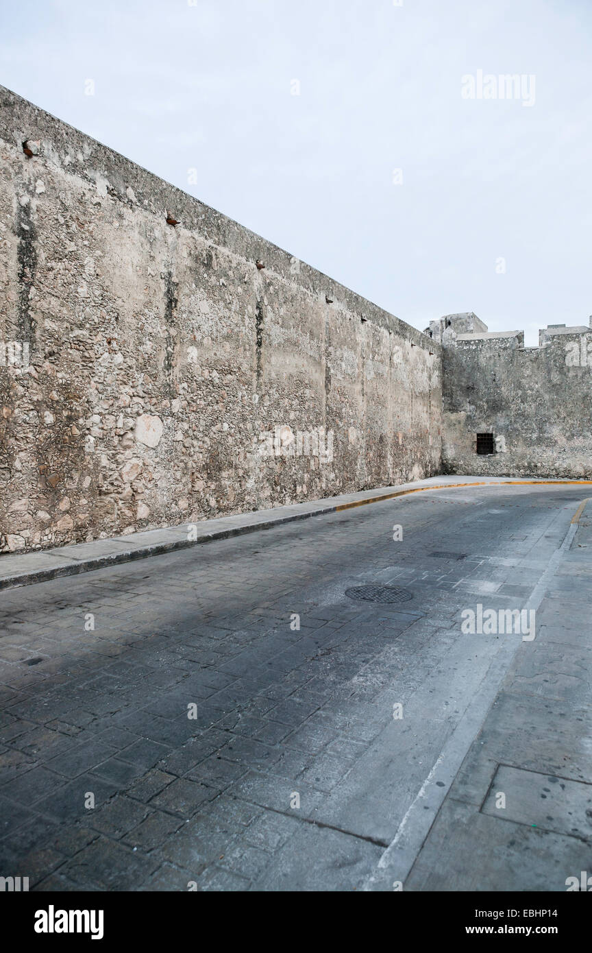 View of historic stone Land Gate wall as it runs along 18th Street  including empty street and clear blue sky Campeche, - Stock Image
