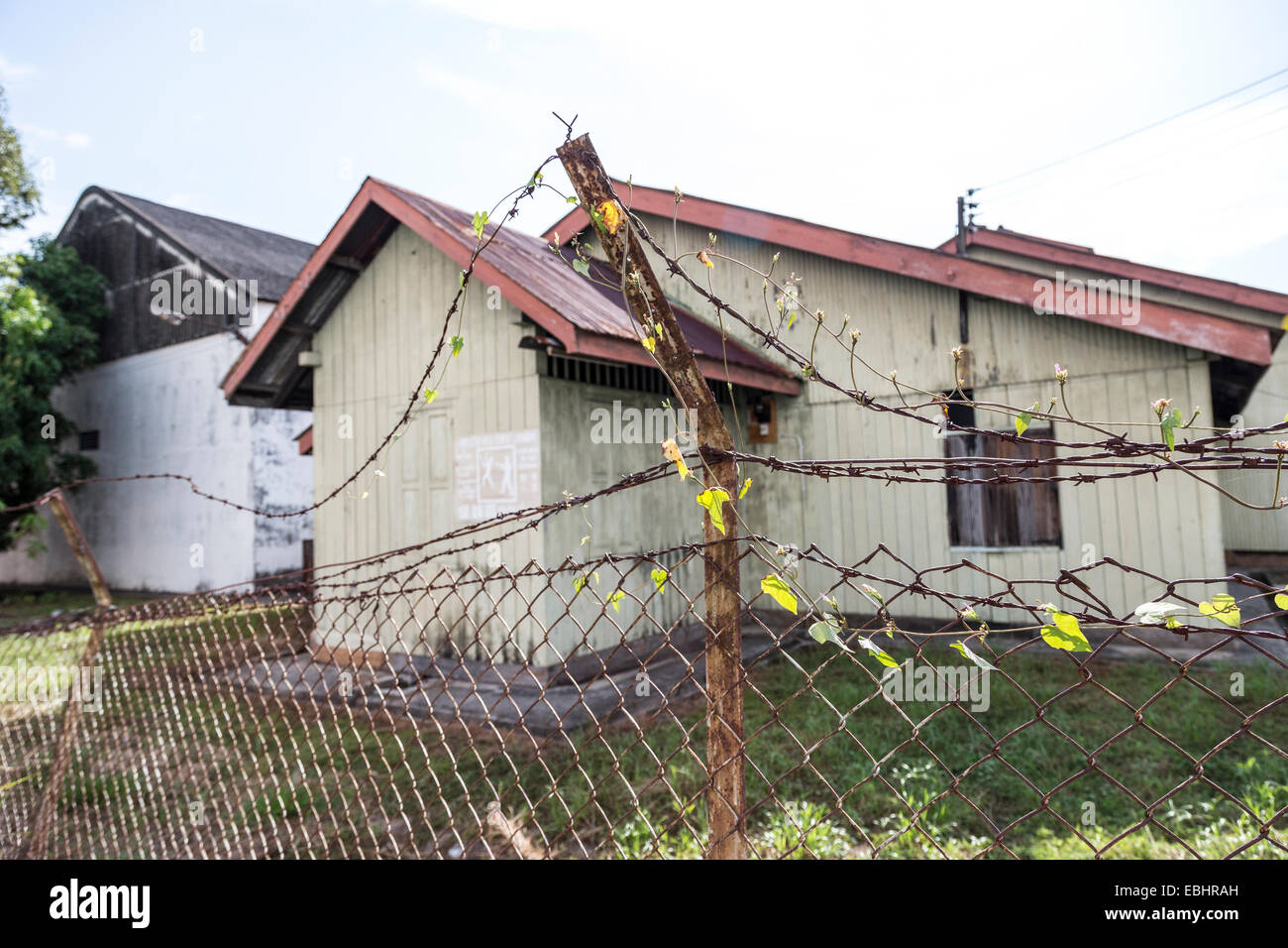 Old barbed wire fence around building, Miri, Malaysia - Stock Image