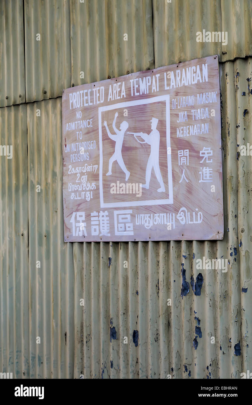 Old security warning sign for protected area with man shooting unauthorised person, Miri, Malaysia - Stock Image