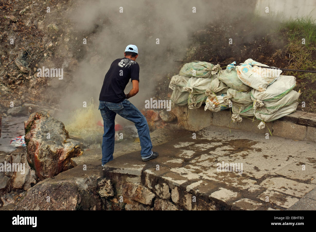 Man cooking sacs of corncobs in a hot spring with naturally boiling water in Furnas, island of São Miguel, Azores, Stock Photo