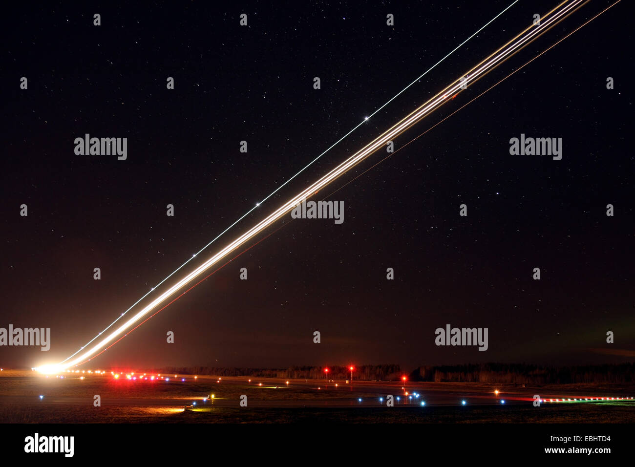 Light trails from an airliner taking off in the night from Skavsta airport, Sweden. - Stock Image