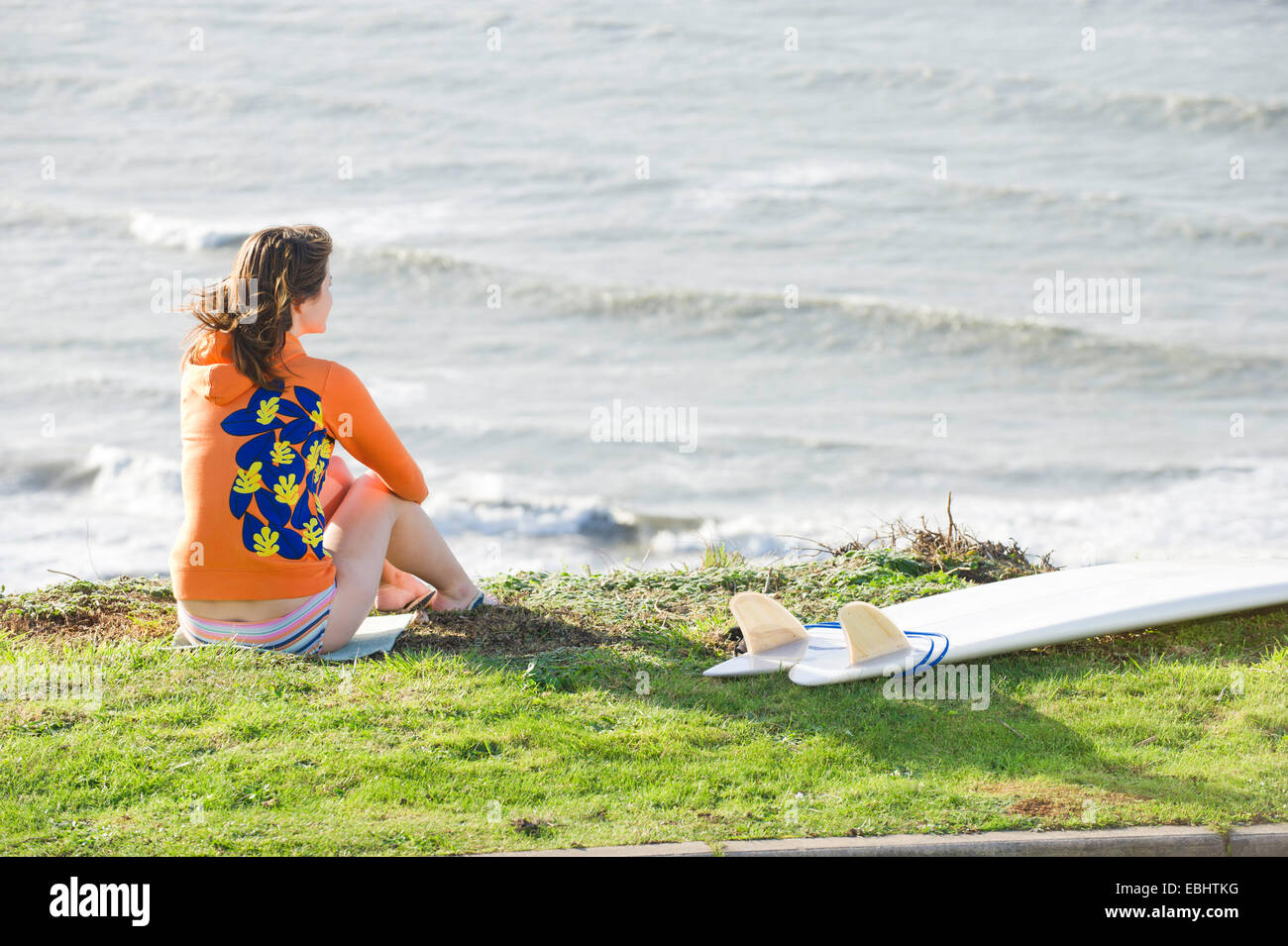Girl surfer looking at waves - Stock Image