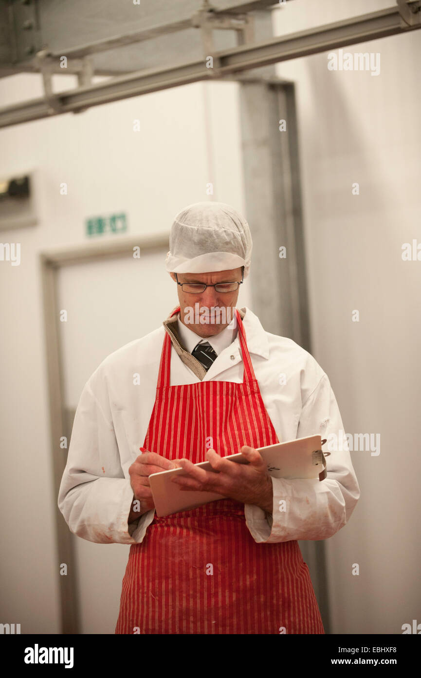 Butcher in a cold room taking notes - Stock Image