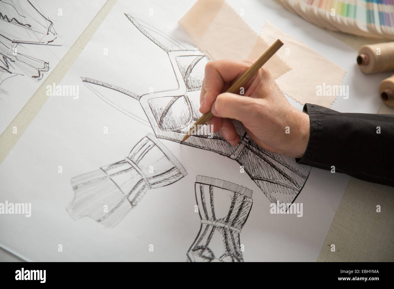fashion designers, working in progress on tailor table - Stock Image