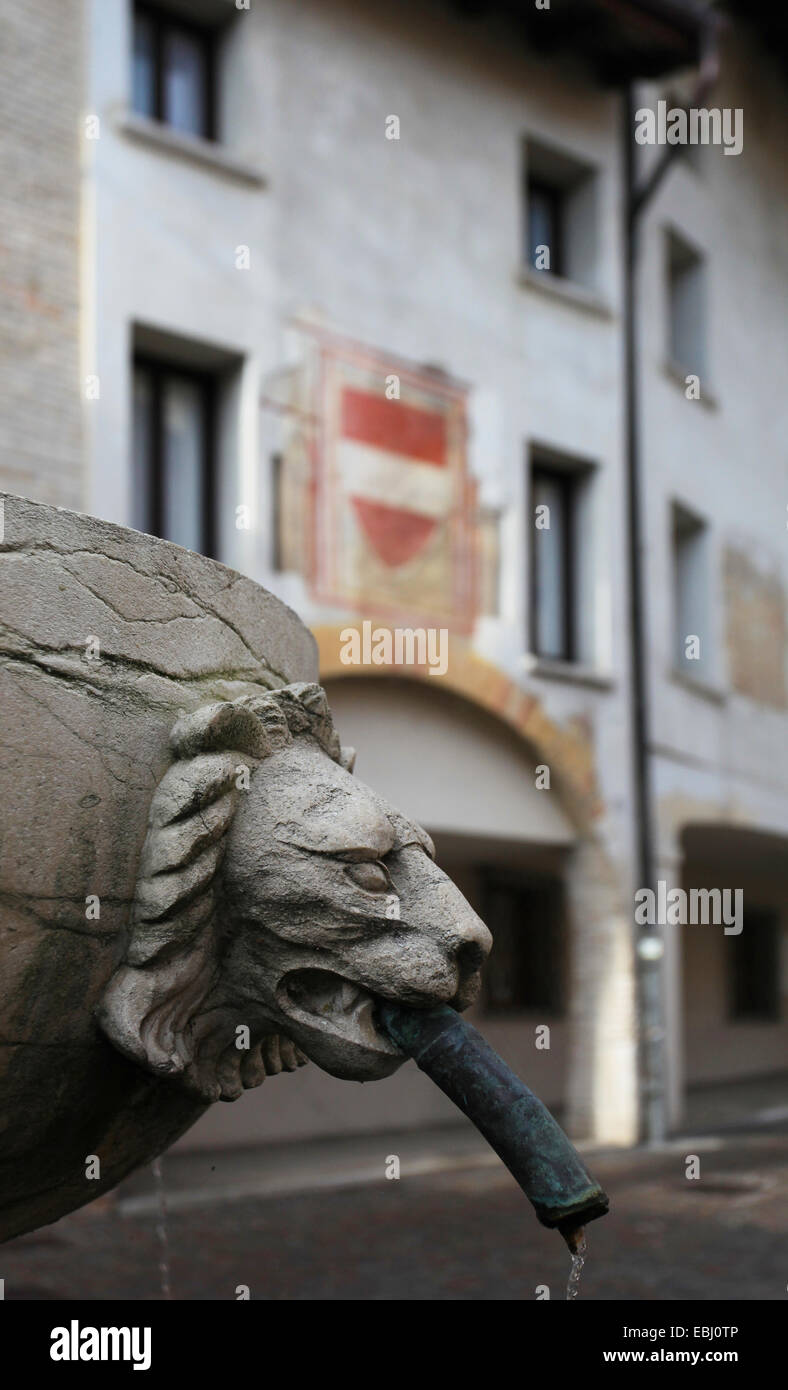 Fountain with lion's head in front of a medieval edifice with fresco depicting the Austrian coat of arms. Old - Stock Image