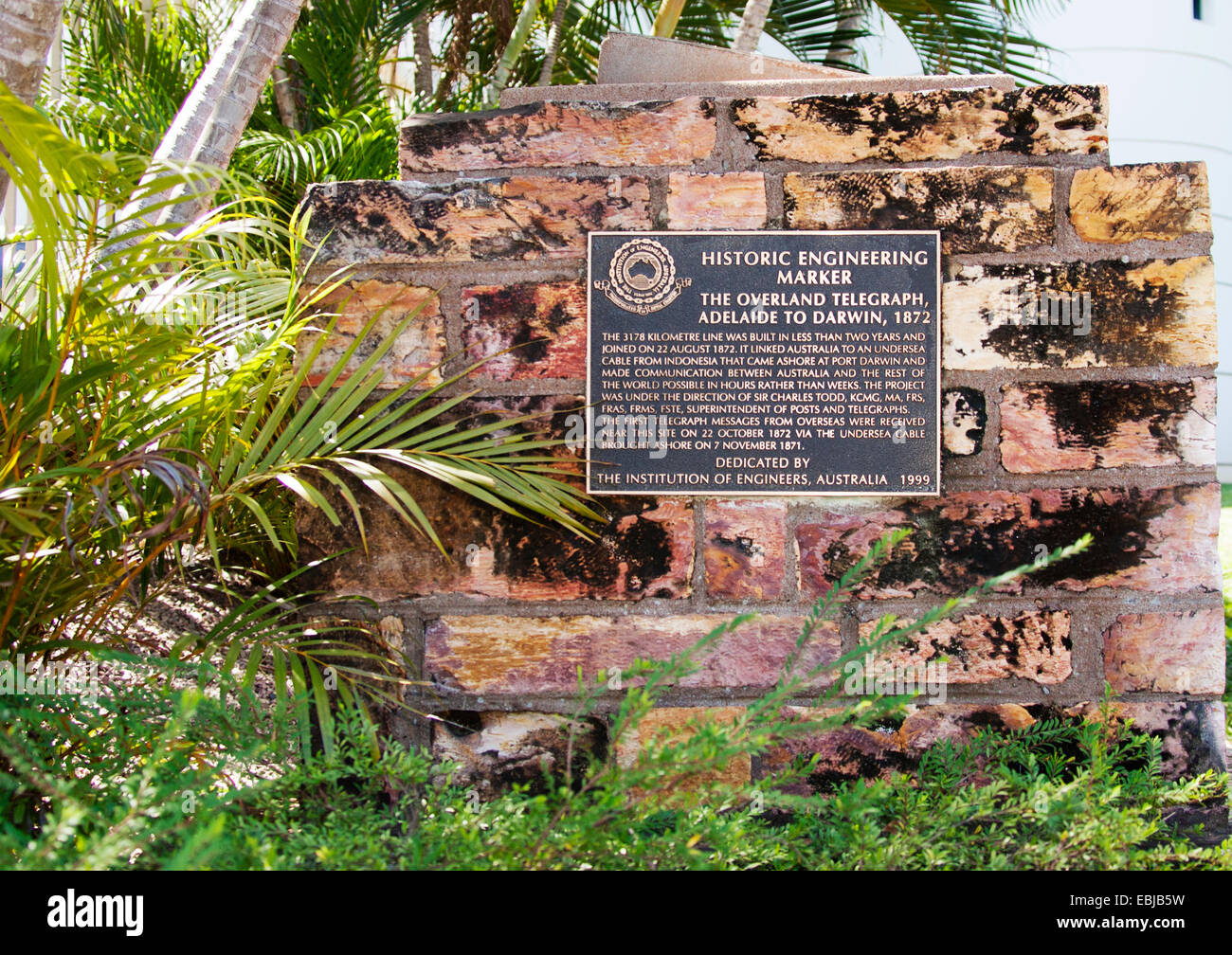 Landscape format shot of the historical monument, set among palm trees, denoting the first Adelaide to Darwin overland - Stock Image