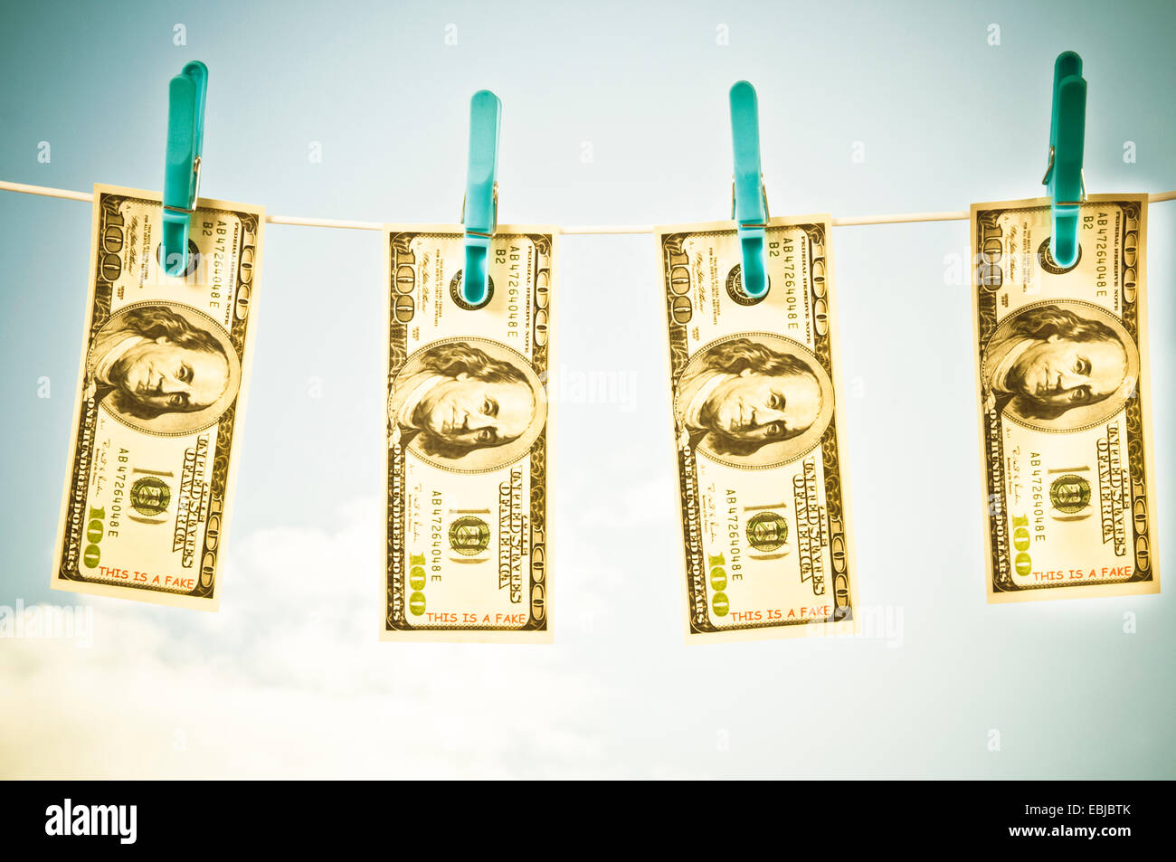 fake dollars banknotes hanging on a rope with clothespins - Stock Image