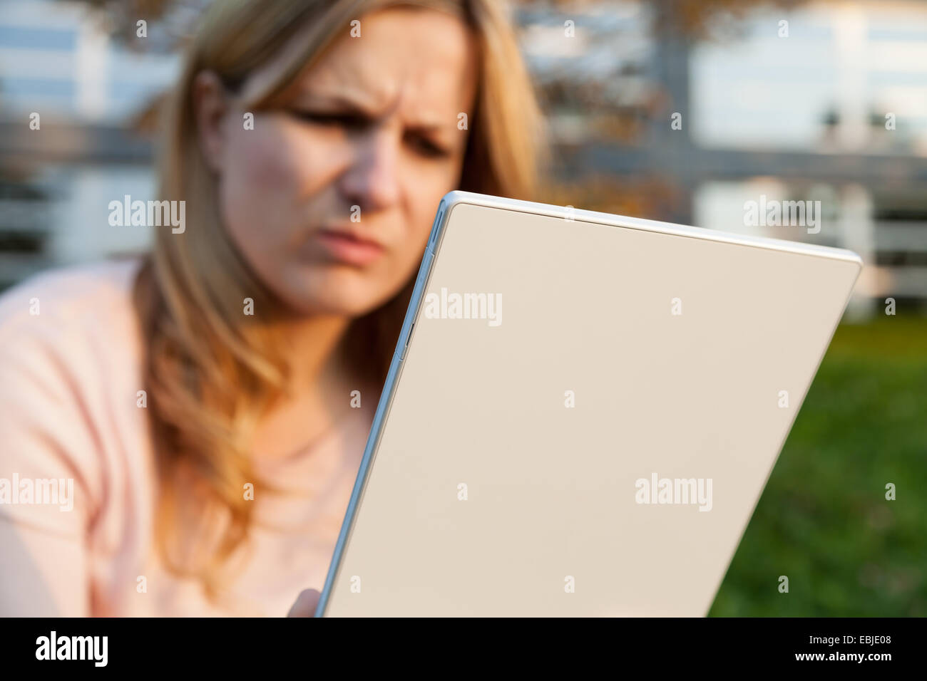 angy woman with a white tablet - Stock Image