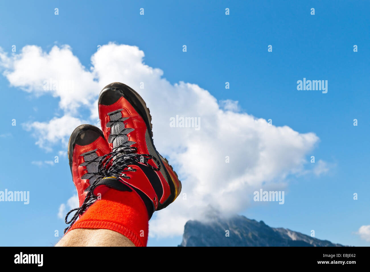 legs with red hiking boots rise up to the sky, Austria - Stock Image